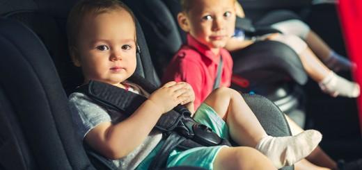 Tres niños sentados en la parte de atrás del coche, mirando a cámara